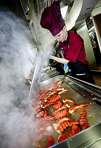 US Navy 111220-N-OY799-224 Culinary Specialist Seaman Jon Ketola grills lobster tails in preparation for the Christmas meal in the aft galley aboar.jpg