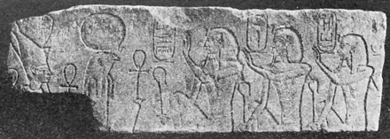 Relief showing three kings looking right, with hieroglyphs around their heads
