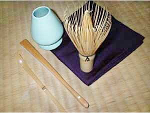 Japanese tea ceremony utensils -  Some implements for tea ceremony.  From bottom left: chashaku (tea scoop), sensu (fan), chasen kusenaoshi (whisk shaper), chasen (bamboo whisk) and fukusa (purple silk cloth)