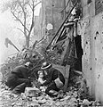 Wardens 'rescue' a young boy from the rubble and debris next to a bomb-damaged house in Fulham during a Civil Defence exercise in 1942. D7895.jpg