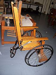 Wooden wheelchair with a single rear wheel