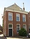 foto van Huis onder schilddak en met lijstgevel, ingedeeld door een middenrisaliet en bakstenen geblokte pilasters