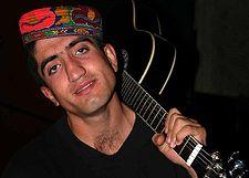 A Tajik guitar player wearing a traditional hat