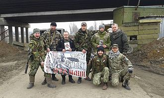 """Yuriy Ruf - Yuriy Ruf holding a """"Дух Нації"""" flag with Ukrainian soldiers at the front line in Donbas."""
