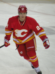 A hockey player in a red uniform with white and yellow stripes at the waist skates forward. His uniform has a white, stylized C logo on the chest and the number 24 on his arms.