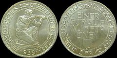 At left, the obverse of shooting thaler, showing a kneeling rifleman aiming to right, surrounded by the inscription EIDGENÖSSISCHES SCHÜTZENFEST IN LUZERN, with 1939 below. At right, the reverse, showing the words EINER FÜR ALLE, ALLE FÜR EINEN above the Lucerne coat of arms in the middle, with EINLÖSBAR BIS 31. AUGUST 1939 around the outer edge, and 5 FR at the bottom.