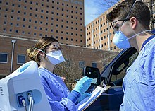 Two medical professionals, one holding a clipboard, in blue scrubs and facemasks stand outside the window of a dark blue car parked in front of a brick building.