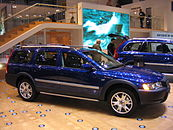 Passenger side view of blue XC70 OR with silver door trim, rocker trim and roof rails