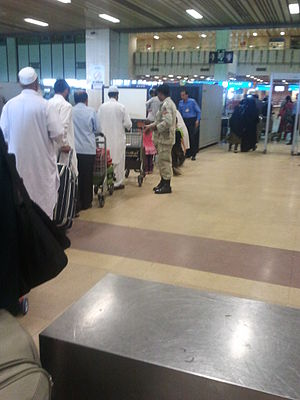 Law enforcement in Pakistan - ANF officer checking passengers at Jinnah International Airport.