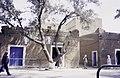 ASC Leiden - van Achterberg Collection - 14 - 01 - La rue principale avec deux photos de Chadli Bendjedid - Tamanrasset, Algérie - 1984.jpg