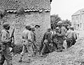 A Platoon of Negro Troops Surrounds a Farm House in a Town in France, as They Prepare to Eliminate a German Sniper Holding up an Advance, Omaha Beachhead, near Vierville-sur-Mer, France - NARA - 531188.jpg