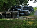 A pile of grass bales in plastic under the shadow of trees; North-Netherlands, 2012.jpg