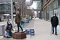 A worker cleans the Mary Tyler Moore statue as a man walks by in a medical face mask in Minneapolis, Minnesota.jpg