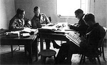 Four men in uniforms it a table reading books and documents.
