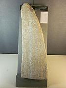 Imposante pierre taillée en forme de dent avec des grandes inscriptions gravées dessus.