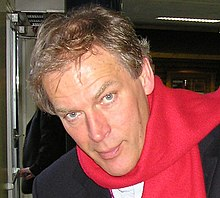 A man with short blond hair and blue eyes wearing a red scarf