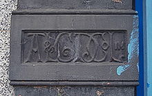 The initials AL&GD Co Ltd in ornate script, carved into a flat column