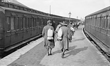 Soldiers walk down a station platform, while on either side of the platform are two trains. The men are wearing slouch hats and are carrying bags over their shoulders