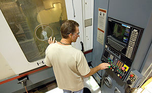 "Machining - A ""numerical controlled machining cell machinist"" monitors a B-1B aircraft part being manufactured."