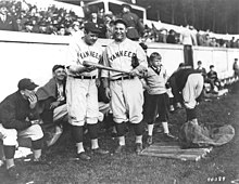 Two men smiling and holding a baseball bat, with a child next to them. Several seated men are sitting behind them, in front of grandstands.