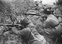 A submachine-gunner and a machine-gunner lying in a trench with their weapons ready and pointing toward the left. In the background, several more soldiers are also lying in the trench and facing left.