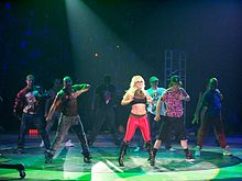 A blond woman female performer wearing a black and red outfit, dancing with a group of men.