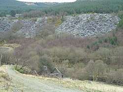 Large spoil heaps of slate appear on the hillside in a heavily wooded area. In the foreground is a small stone house, without a roof.