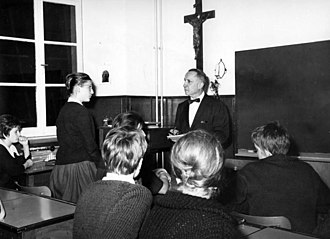 This 1961 picture shows a student standing up, to answer the teacher's question. On the wall is a Christian cross, then commonly found in a gymnasium classroom, but now less frequent. In 1995, a court ruled it violates the rights of non-Christian students and must be removed if any student objects. Bundesarchiv B 145 Bild-F010220-0009, Bad Honnef, Gymnasium Nonnenwerth.jpg