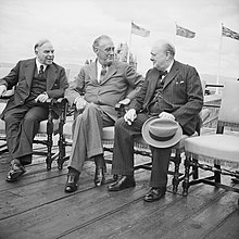 The three leaders sit on chairs on a wooden deck. Their national flags fly in the background.