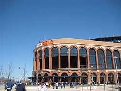 "The exterior of a baseball stadium, which has a round brown entrance area with a white and orange ""citiFIELD"" on top."
