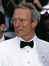 Photographie de Clint Eastwood au Festival de Cannes en 1994. Il est vêtu d'un costume blanc et d'un nœud papillon; il sourit légèrement, regardant sur le côté