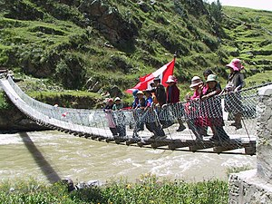 Chumbivilcas Province - Children are waving the Peruvian flag on the new footbridge across Qañawimayu in Qullpatumayku, Chumbivilcas Province