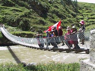 Chumbivilcas Province - Children are waving the Peruvian flag on the new footbridge across Qañawimayu in Qullpatumayku, Chumbivilcas Province