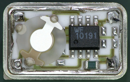 Inside a modern DIP package quartz crystal oscillator module.It includes a ceramic PCB base, oscillator, divider chip (/8), bypass capacitor, and an AT cut crystal. Crystal Oscillator DIP Module Teardown.png