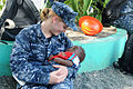Defense.gov News Photo 100727-N-7680E-232 - U.S. Navy Yeoman 2nd Class Rachel Martis assigned to the amphibious assault ship USS Iwo Jima LHD 7 cradles a Haitian child during a community.jpg
