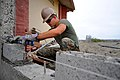 Defense.gov News Photo 110517-F-ET173-147 - U.S. Marine Corps Cpl. Joe Everetts checks to see if a brick is level while constructing a wall for a new roof at a school during a Continuing.jpg
