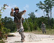 Defense.gov News Photo 110721-A-DK678-581 - A U.S. Army soldier throws a grappling hook to clear a potential mine field before advancing during a field training exercise at Fort Bragg N.C.