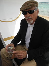Dennis Hopper, with gray hair and a gray goatee, wearing a hat and sunglasses
