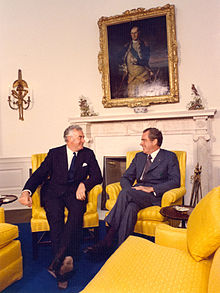 Whitlam sits in a chair, smiling, with Richard Nixon (whose appearance is well known) in another, who is also smiling.