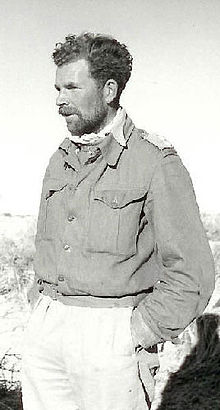 Black and white picture of a man with a short beard wearing a buttoned jacket and light-coloured trousers, facing left with his hands in his pockets