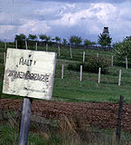 "Behind a faded white sign saying ""HALT ZONENGRENZE"", there is a derelict barbed-wire fence supported by leaning wooden posts; some distance behind that, there are two newer-looking barbed-wire fences supported by concrete posts. Another fence and a guard tower are visible in the distance."
