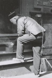 A black-and-white photograph from three-quarter back view of a man wearing a round cap and a long braided queue that reaches to the back of his right knee. His left foot is posed on the first step of a four-step wooden staircase. Bending forward to touch a cylindrical container from which smoke is rising, he is resting his left elbow on his folded left knee.