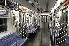 The interior of an R142A car on the 4 train. The seats are painted blue. Above the seats, advertisements can be seen.