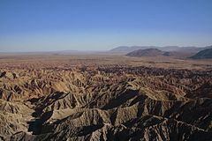 The shot is of a barren desert environment. There are several canyons, and it is framed against a blue sky.