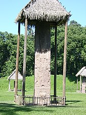 A tall, narrow monument covered by a thatched roof. Two further stelae are visible in the background, also covered by thatched roofs, against a backdrop of trees.