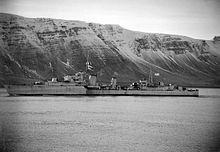 """Niszczyciel HMS """"Bedouin"""" widziany z lewej burty płynie wolno w islandzkim fiordzie. Na burcie widoczny znak taktyczny G67. W tle wysokie skały fiordu."""