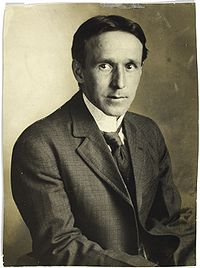 A seated man, wearing a suit and tie