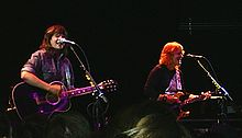 Indigo Girls strumming guitars onstage