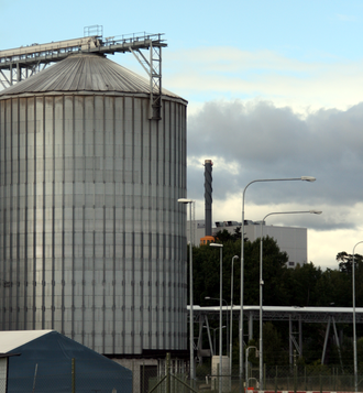 Industrial ecology - Example of Industrial Symbiosis.  Waste steam from a waste incinerator (right) is piped to an ethanol plant (left) where it is used as in input to their production process.