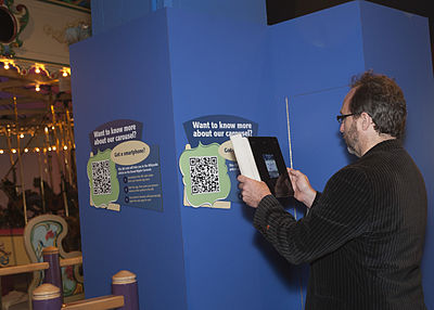 "Jimmy Wales using an iPad to read the Wikipedia article ""Broad Ripple Park Carousel"" after scanning it on the nearby QRpedia sign"